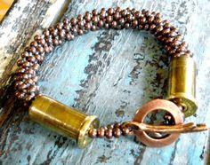 Designed and made by Renee Phillips  Kumihimo beaded braid, copper toggle with brass bullet shell casings!