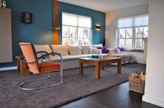 woonkamer met blauwe muur, gispen stoel en witte bank  Stylist en ...