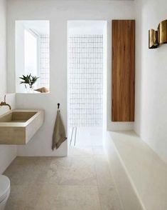 Que tons você escolheria para trazer leveza ao espaço? Neste banheiro de Sarah Davidson para uma residência em Sydney, na Austrália, o branco foi combinado com revestimentos neutros e toques pontuais da madeira para não interferir na atmosfera clean. Foto: Prue Ruscoe