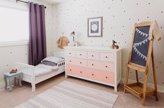 Sweet nursery features twin ned dressed in white and grey bedding placed under window dressed in purple grommet curtains beside Ikea Hemnes 8-Drawer Dresser accented with pink ombre drawers alongside white and gray striped rug and chalkboard on easel.