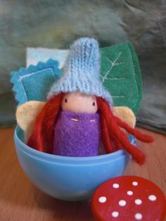 What a great idea! Fill a plastic Easter egg with tiny treasures. The egg here is filled with a little handmade berry colored fairy with a wool felt tunic & felt wings, a leaf bed & turquiose pillow, a mushroom stool, 1 tiny mushroom, a small felted-sweater rug, 3 magic pebbles & a small wooden Easter Egg which all fit snuggly into the big plastic egg,