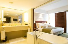 The deluxe studio bathroom is an open space with a separate walk-in shower and a televisio...