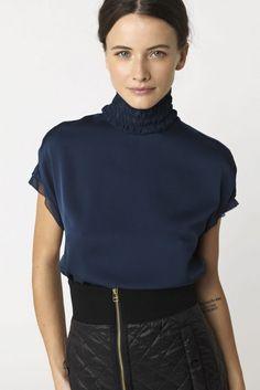 Blå silke selskapstopp med trendy polohals fra By Malene Birger. Laget av 92% Silke 8% Elastan.