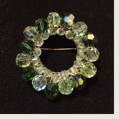 "Vtg Two-Tone Green Glass Crystal Wreath Brooch Pin A dazzling display of sparkling green crystals on a silver-tone rolling-c clasp setting. The inner circle has small mint-green multi-faceted glass crystals and the outer circle in an alternating pattern of larger glass crystals in a darker green and mint green. Measures 1-3/4"" in diameter. In excellent preowned vintage condition. Vintage Jewelry Brooches"
