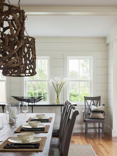 Lovely dining room features driftwood chandeliers illuminating long rectangular dining table lined with gray x-back dining chairs atop a bound sisal rug situated across from a glossy black sideboard table.