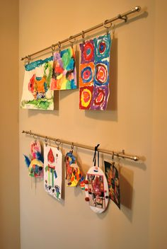 Art display using simple cafe rods with clip rings: with this idea the wet art works don't have to touch the walls which is another great option. (where do you find the clip rings though?)
