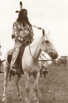 American Indian on his horse. From the background, the men and the wagon looks like it was about late 1800's.