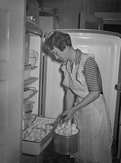 Farm wife, 1942,  keeping eggs, fresh from the hen house, in a refrigerator. Note the earthenware milk pitcher