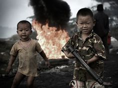 Burmese refugee children play war games as piles of garbage and tires burning around them emulating a battlefield at the dumpsite in Mae Sot border town, northern Thailand (Narciso Contreras)