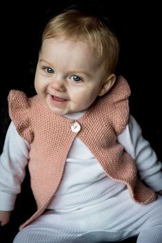 129/2 Smart babyvest med flæseærmer strikket i Mayflower Easy Care. Smart lille vest til piger i alderen 0-3 mdr, 3-6mdr, 12 mdr og 24 mdr.