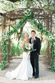 The Sacred Oaks Arch embellished with garland trailing to the ground with white roses, hydrangeas and dahlias accenting the sides and the center of the arch | Whim Florals | Camp Lucy | Sacred Oaks | Green Wedding | Photo Credit: Heather Rowland Photography