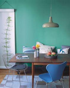 Goede trendy setting: 1. opvallende kleur op de muur. 2. verschillende stoelen. 3. dun vloerkleed. 4. lamp. 5. bankje in de eethoek met verschillende kussens.: