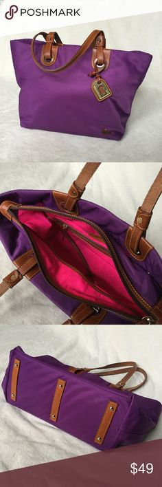 """Dooney Bourke Nylon Grommet Shopper Tote Nylon grommet shopper tote from Dooney and Bourke. Purple nylon outer with embroidered duck. Neon pink interior with leather handles. In excellent condition except for two marks on the front exterior, as shown. Very clean interior. Measures 17.5""""w by 11.5""""h by 6""""d. Dooney & Bourke Bags Totes"""