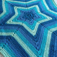 A beautifully bright and vibrant crochet star blanket in varying shades of blue.