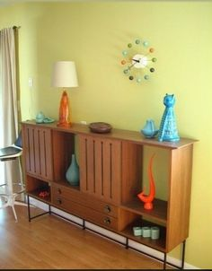 Love everything about this photo:  the credenza, the clock, the stool, the knick knacks.