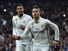 Real Madrid's Colombian midfielder James Rodriguez (R) celebrates past Real Madrid's French defender Raphael Varane after scoring on a penalty kick during the Spanish Copa del Rey (King's Cup) round of 16 first leg football match Real Madrid CF vs Sevilla FC at the Santiago Bernabeu stadium in Madrid on January 4, 2017. / AFP / GERARD JULIEN