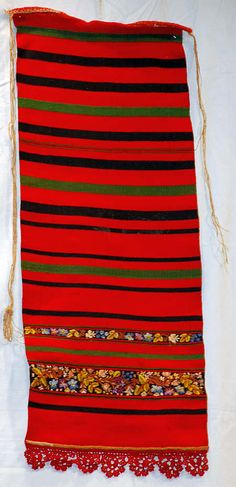 Some of the bands in this apron are woven.  Others are embroidered.  This style of apron is worn in the Nasaud region where the peahen and peacock headwear is worn.