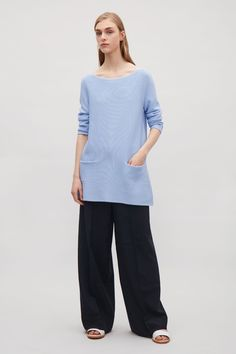 Flaring towards the hemline for an A-line shape, this jumper is made from knitted cotton. A tunic length, it has a wide round neckline, 3/4 sleeves and inverted front pockets.