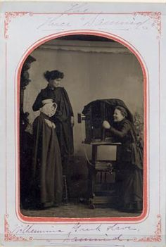 """Above  is a tintype of three young women posed with a large studio camera. The cryptic writing reads """"The Three Damnid"""" or """"Danmid"""" Wilhemina Greek Slave & Damnid or Danmid"""""""