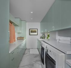Mint gloss cabinets are a breath of fresh air in this laundry room by Millennium.