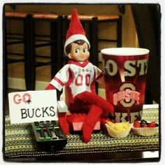 Buckeyes jersey ✔ Recliner ✔ Remote ✔ Spirited Sign ✔ Snacks ✔ Giant-sized adult beverage ✔ Yep, Manny the Elf on the Shelf ready for the big Ohio State Buckeyes game! All he needs now is an - - .... ! ! !