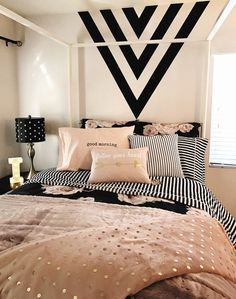 Girls room. Black, gold and pink. Black paint feature wall. Black and white stripes. Design with arrows. Soft pink and black. Bed of roses.