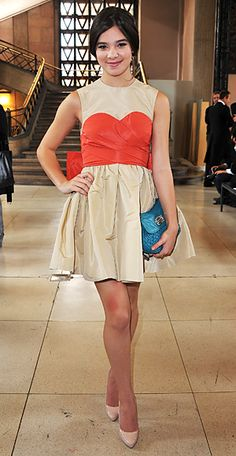 Hailee Steinfeld in an ivory Miu Miu design with a pieced-in coral bustier, a contrasting turquoise clutch, also from the brand.
