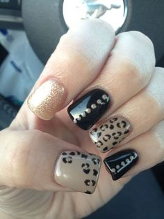 Leopard print nails with black, rhinestones, and glitter.