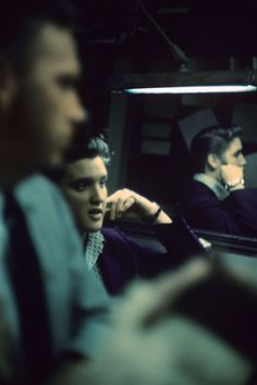 Elvis in a Press Conference   Presley is interviewed by the press before his appearance on Steve Allen's variety show on July 1, 1956, backstage at New York's Hudson Theatre. His image is reflected in the mirror to the left in the room, which was dimly lit by one fluorescent lamp.