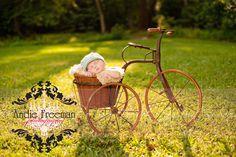 Newborn baby boy in vintage tricycle wearing baby blue newsboy hat.  Outdoor newborn session.  www.TheAthensNewbornPhotographer.com