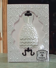 Stampin' Up Label Love Wedding Dress card. was made using the All Dressed Up framelits die by Stampin' Up. The dress has been cut out and layered several times and is mounted on a black dress form. The center is die cut using the Labels 20 by Spellbinders, I embossed the rest of the panel using an M-Bossabilities folder by Spellbinders. I have also changed the inside up a bit, by attaching the die cut center, which I mounted on another piece of black card stock.