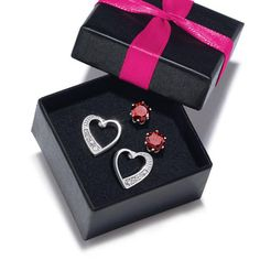 Two pairs of silvertone pierced earrings in a gift box:• Heart studs with rhinestones with Post and Butterfly Clutch• 1 1/2-carat* red CZ studs with Post and Butterfly Clutch • Imported
