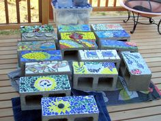 Mosaic Tiling examples for Cinder Block Edging.  The open chambers of the Cinder Blocks can be used for growing herbs and annual plants along your garden border.  Perfect for Marigolds and other mosquito repellent plants.  Take this to another level by gluing pennies (copper) around the rim to prevent slugs and snails from entering your veggie patch!!
