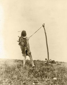 Edward S. Curtis photographed this Crow (Apsaroke) man, leaning back slightly, with strips of leather attached to his chest and tethered to a pole secured by rocks, participating in the piercing ritual of the Sun Dance that lasted at least four days; a dancer could not be freed until he experienced a vision.  – Courtesy Library of Congress –