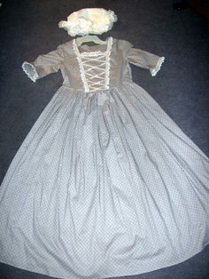 The dress is made from gray cotton calico fabric with gray dots and swirls all over it. Dress has white lace and white satin ribbon trim on bodice, neck and sleeves. There is a back zipper for ease of use. White Satin, White Lace, Girl Costumes, Halloween Costumes, Hamilton Costume, Calico Fabric, Costume Dress, Satin Dresses, Swirls