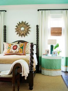 mint ceiling, table skirt matches curtain, black curtain rods, sunburst mirror in the middle of gorgeous bed posts, rectangular lamp, and grass shade, nice