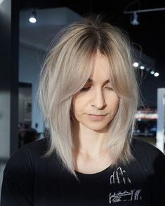 This Shaggy Curtain Banged Lob with Undone Straight Texture and Platinum Blonde Color Medium Length Hairstyle is a great cut for someone seeking trendy modern style. This shoulder bob cut can be styled sleek and straight, with textured waves or curls, or with a simple blowout for body and movement. It is also long enough to create updos and braids. Styling tips for this long bob and other similar medium length haircuts, lobs, and hair color ideas can be found at Hairstyleolog