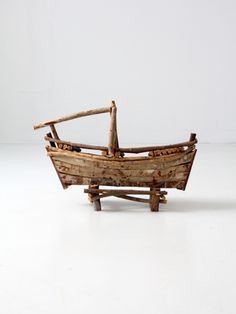A vintage folk art twig boat. The rustic twig and stick boat sets on a wood frame. A hand built piece with great character. - rustic, twig and stick boat on a wood frame - great age and tone to the wo
