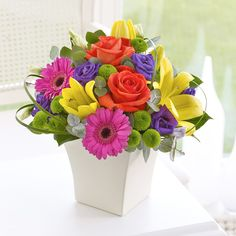 This vibrant vase arrangement contains red roses and pink germini.