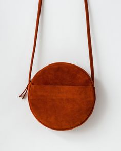 A leather circle purse with top zipper closure and adjustable leather strap. Exterior pocket for easy stashing, and two interior pockets for organization. Leather Purses, Leather Handbags, Leather Bags, Unique Birthday Cards, Circle Purse, Fabric Bags, Sew Bags, Brighton Handbags, Suede Fabric