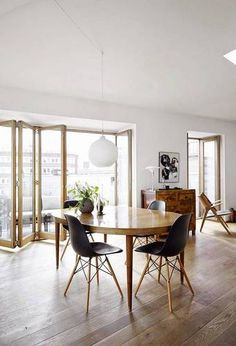 danish interior design wood floors in white dining room with black chairs