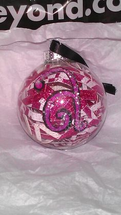 Christmas ornament, paint glitter, scrapbook paper and ribbon. Stuff a clear glass ornament with strips of scrapbook paper and paint.