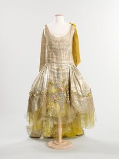 "1925 Boué Soeurs Court Presentation Dress. Protocol regulated the formal attire for men and women who were to be presented at the Court of St. James in London, until the custom was ended in the 20th century. The long train emanating from the shoulders of this gown suggest it may have been worn for a court presentation in the mid-1920s. An example of the silhouette known as a ""robe de style,"" in which interior boning widens the skirt at either side, the dress was custom-made"