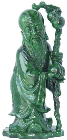 """CHINESE EMERALD GREEN GEM JADE SHOU FIGURE Executed in meticulous detail this figure is depicted standing with wooden staff and double gourd hanging from staff. In his right hand is a peach. Fine even deep green jade coloring throughout with smooth and polished finish. Measures 21"""" height x 10"""" width x 7 1/2"""" depth"""