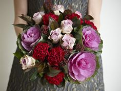 Victoria Plum bouquet ofbrassicas, lilac roses, burgundy carnations and crimson skimmia, with dark cordyline foliage.
