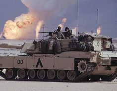 An M1 Abrams tank in the foreground with oil fires burning in the background in Kuwait, February 1991.