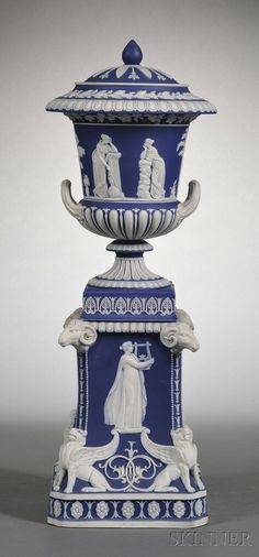 Wedgwood Dark Blue Jasper Dip Covered Vase on Stand, England, 19th century, applied white relief, the cover with foliage; the vase with classical figures with fruiting grapevine and gadroon borders; the stand with ram's heads and griffins to the corners of paneled sides with classical figures, a floral border along the foot.