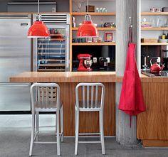Quatro arquitetos trabalharam na transformação de uma casa dos anos 60, no Rio de Janeiro: Cynthia Issa, Rogério Cruz, Silvia Cavalcanti e Flavia Torres. Na cozinha gourmet, um dos pilotis é envolvido pela bancada do ambiente. Detalhes em vermelho quebram o predomínio do cinza e da madeira