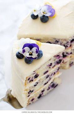 Tender butter cake with brightened with lemon juice, lemon zest and wild blueberries, frosted with a tangy sweet lemon cream cheese frosting. and Drink deserts dessert recipes Lemon Blueberry Cake Brownie Desserts, Just Desserts, Delicious Desserts, Dessert Recipes, Yummy Food, Yummy Snacks, Cupcake Recipes, Purple Desserts, Dinner Recipes