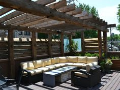 This backyard deck features a large pergola and plenty of seating. An outdoor sectional, complete with plump yellow cushions, invites guests to linger in the shade of the rustic hardscape. The rooftop design features tropical hardwood decking, reclaimed timber, glass panels, louvered slat screening, custom fire pit, sectional and lounge chair.
